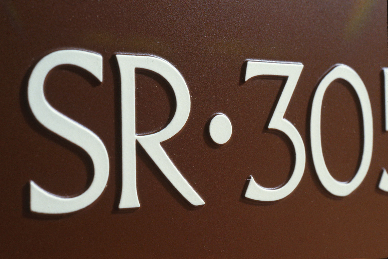 Closeup of two letters and two numbers using this font on a sign.