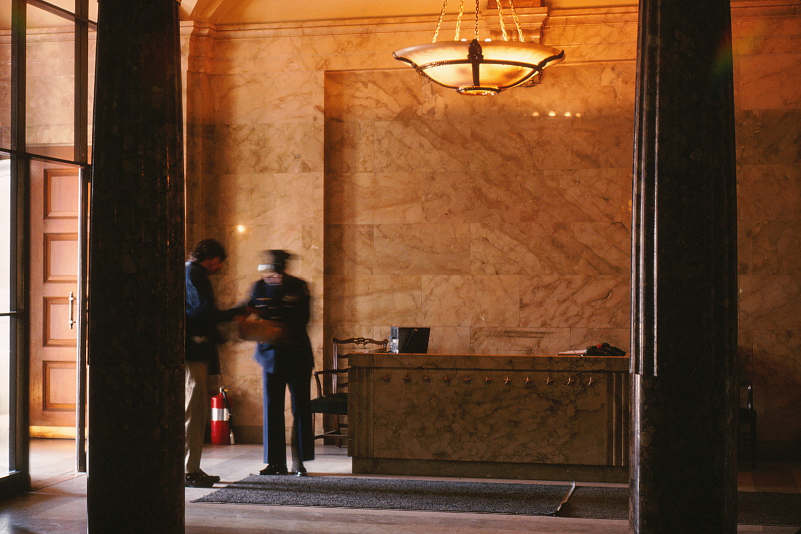 Photograph of the Capitol lobby featuring two guards and the main security desk