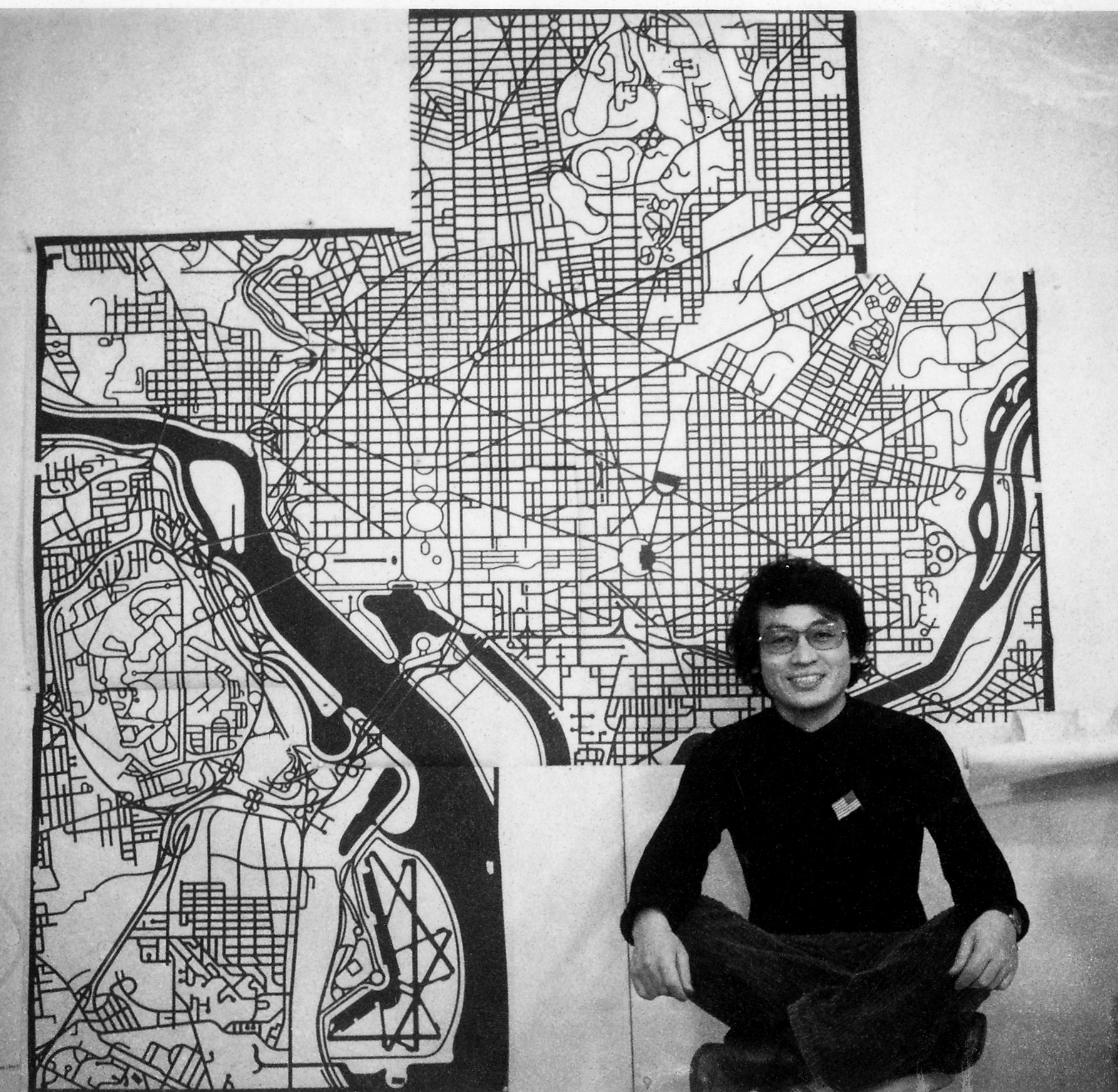 Aki sitting in front of map cutouts