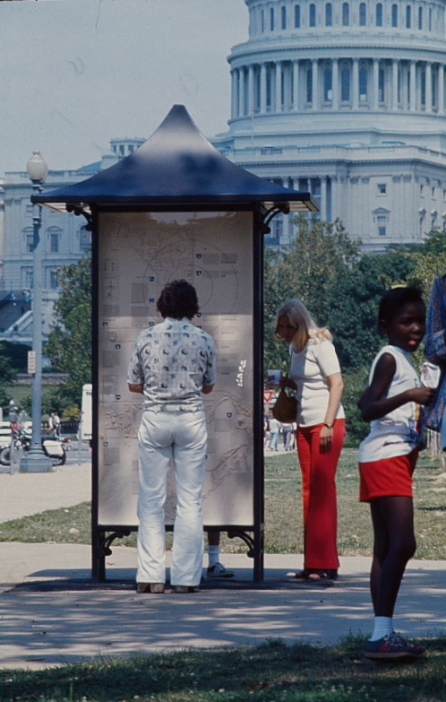 People looking at kiosk by Capitol building